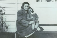 Jo Ann Dobecki Shopbell, CSC, SC:L, NAD V (as a small girl) and her mother, sitting on front steps of a house. black and white photo