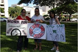 "Three people holding signs for rally ""Honk for independent Living"", ""myself we can"", and ""save services"""