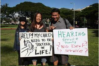 "Holding signs ""help! my child needs to succeed in life"" and ""hearing service plenty no deaf service?"""